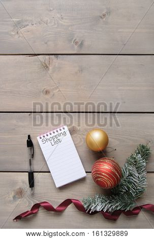 Christmas shopping list over a wooden background