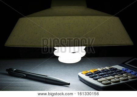 Lamp, Silver pens and calculator on the desk on black background.