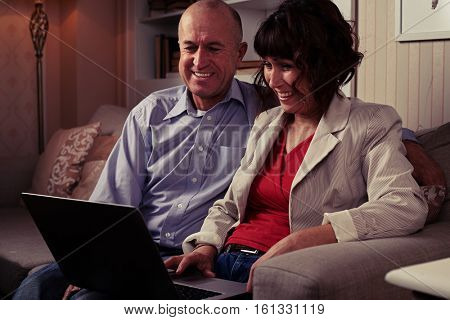 Side mid shot of an elderly pair watching in laptop on the umber settee. Man and woman dressed mainly in classics