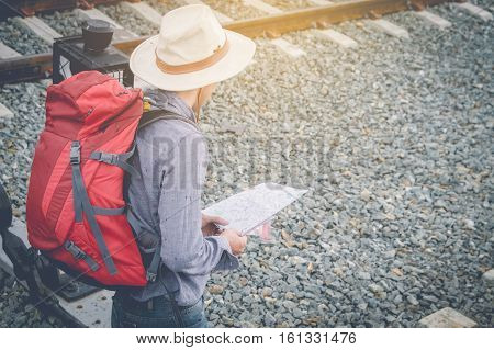 Traveler with backpack and map on train station vintage tone. travel concept.
