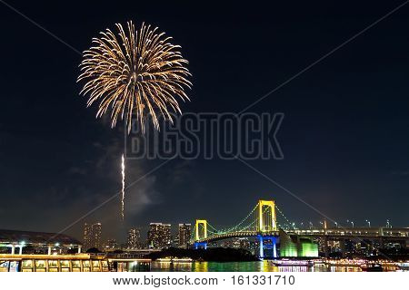 Nightview of Rainbow Bridge and fireworks in Tokyo, Japan.