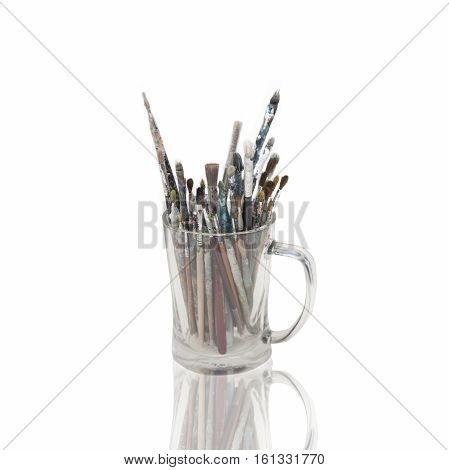 Glass Cup Full Of Paint Brushes Isolated On White Background