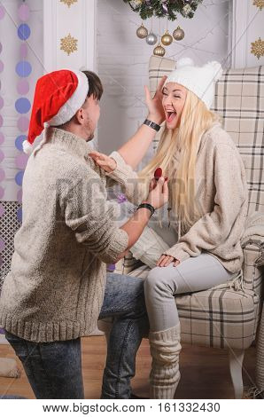 Romantic engagement (marriage) proposal on Christmas eve happy young people in love - love and engagement concept