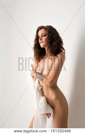 Nude brunette posing in studio with white lace neglige in her hands