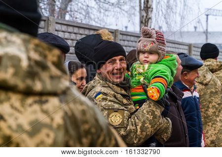 Chop Ukraine - December 6 2016: A soldier holding a child enjoys received a new apartment during the presentation ceremony of the keys. On this day in Chop 23rd soldiers who served in the ATO it was handed the keys to new apartments.