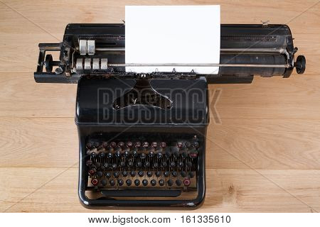 Vintage typewriter with paper sheet on wooden table top view. Old writing equipment. Press, blogging and journalism concept background