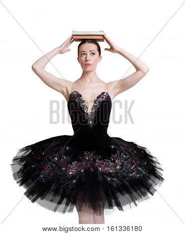 Graceful ballerina making exercise for training ballet posture against white background, isolated. Professional dancer in black tutu skirt with books pile on head. Choreography classes concept