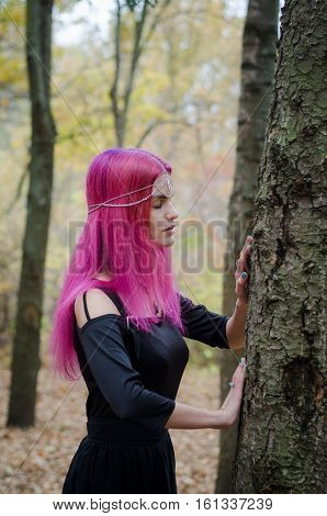 Young witch with pink hair in an autumn forest exchanging energy with a tree magic ritual faded colors