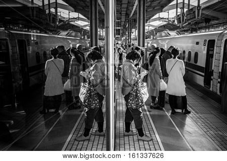 KYOTO, JAPAN - NOVEMBER 12, 2016: People waiting for train on the train station in Kyoto, Japan. West Japan Railway (JR West) is one of the biggest railway companies in Japan.