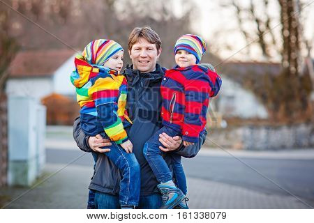Active father holding his children, two little funny kids boys on arm, on cold day. Man and boys walking together in a park in spring or autumn. Happy, joyful family. Dad and sons, best friends.