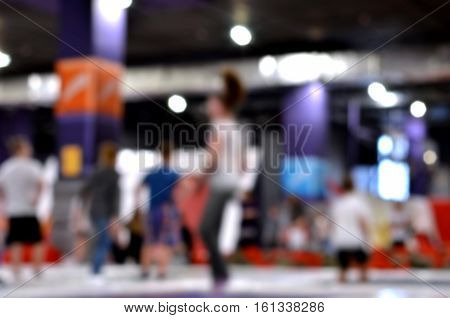 Blurred background. Young people and kids jumping on a trampoline.