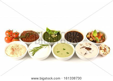 Set of 8 savory sauces and toppings isolated on white. Spoons dipped in the sauces. Soy sauce, curry, mustard, barbecue sauce. Set for menu. top view