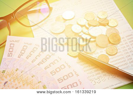 Business, finance, investment or savings concept : Savings account passbook, Thai money , coins, eye glasses and pen on green background