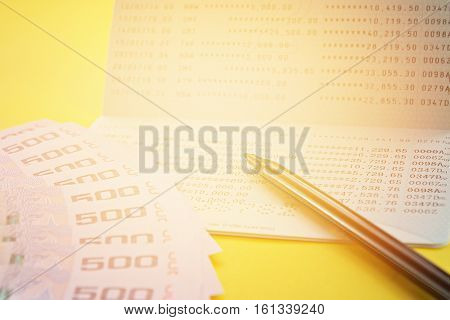 Business, finance, investment or savings money concept : Savings account passbook, Thai money and pen on yellow background