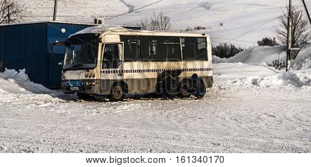 Kazakhstan, Ust-Kamenogorsk, december 8, 2016: Chinese bus Faw at a bus stop. Two men repairing the car, bus, city bus, public bus, mini bus, short bus, old dirty bus, old bus, grunge bus
