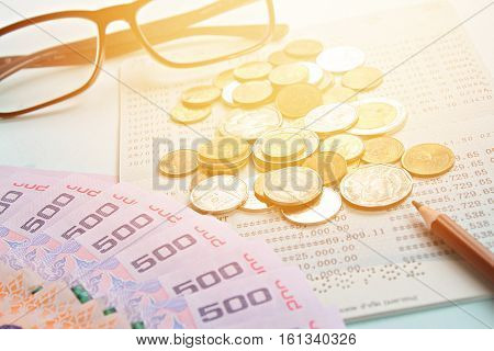 Business, finance or savings concept : Savings account passbook, Thai money, coins, eye glasses and pen on blue background