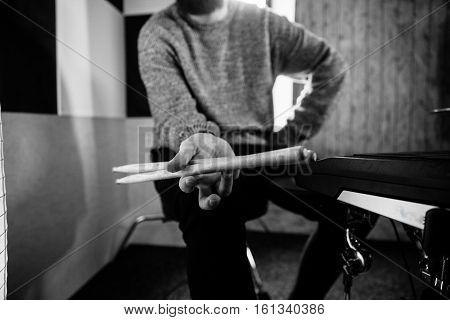 Drummer. The guy holding the drumsticks in his hand. Young man with drumsticks. A bearded man holding a stick in his hands& Black and white photo& Space for text