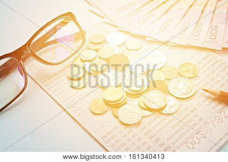 Business, finance, investment or savings concept : Savings account passbook, Thai money, coins, eye glasses and pencil on blue background