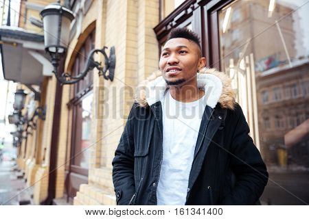 Picture of a handsome african young man walking on the street. Looking aside.