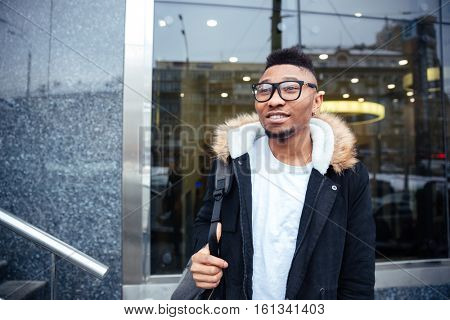 Image of a cheerful african young man walking on the street. Looking aside.