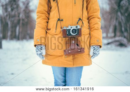 Stylish woman photographer with retro camera in winter park