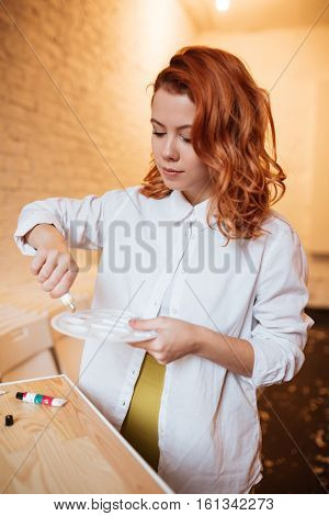 Photo of incredible redhead young woman painter with oil paints and palette. Look at palette.