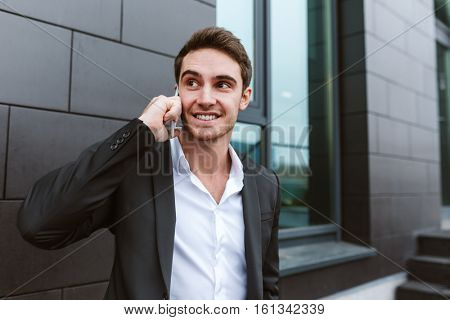 Business man in suit talking on phone and standing near the office