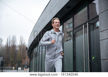 Man in gray sportswear running on the street. From below image
