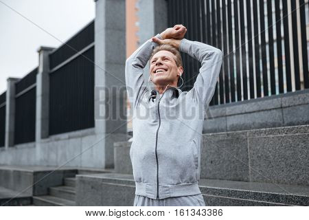 Young runner in gray sportswear and headphone warming up on the street with hands up.