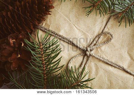 Gift wrapped craft paper with pine cones and fir branches top view New Year concept