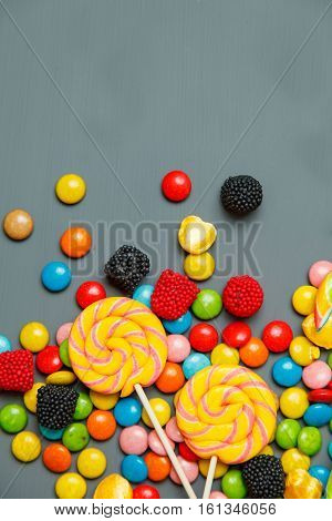 Colorful Lollipops, Candy Canes And Sweet Candies Mix On Gray Wooden Background