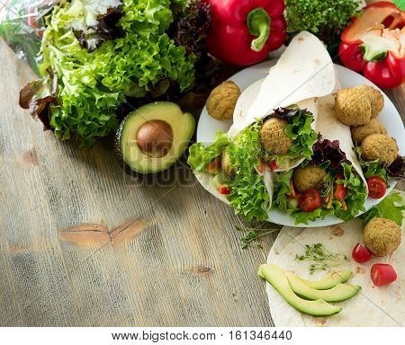 Tortilla wrap with falafel and fresh salad vegetarian healthy food vegan concept