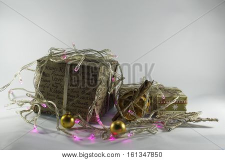 Christmas gift boxes with ribbons and garlands, festive lights, cinnamon, dried orange  on a white background