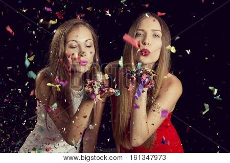 Two beautiful young women having fun at a party blowing away confetti and sending kisses