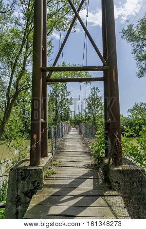 Old steel cable and wooden footbridge across river. Wooden suspension bridge.