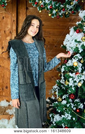 young woman decorates the Christmas tree.