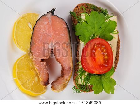Grilled fillet of red salmon fish with cheese and fresh vegetable salad and lemon.