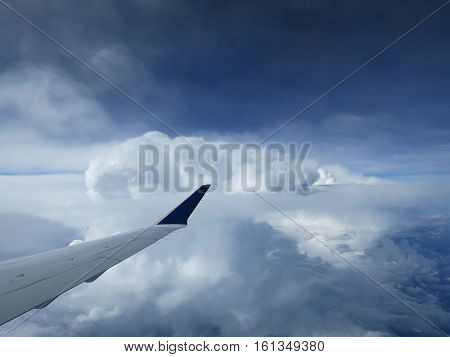 The view from an airplane reveals the tip of its wing and the top of a billowing cloudscape.