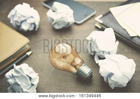 light bulb papers pen and pocketbook on wooden table