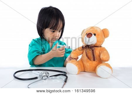 Asian Chinese Little Doctor Girl Giving Injection To Teddy Bear
