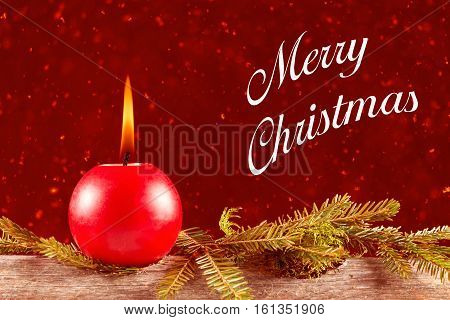 Closeup of red burning candle on merry christmas card