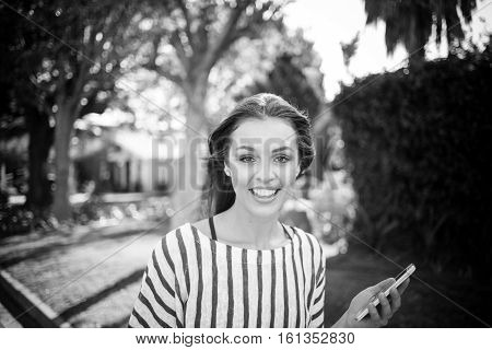 Pretty brunette business woman working / talking and texting on her smart phone while out and a bout in a suburb