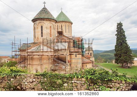 Historical landscape with walls of the monastic complex Gelati in scaffolding in Georgia. Gelati monastery was built in 12th century UNESCO World Heritage Site.
