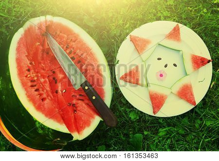 big ripe water melon with slice and knife outdoor sunny photo