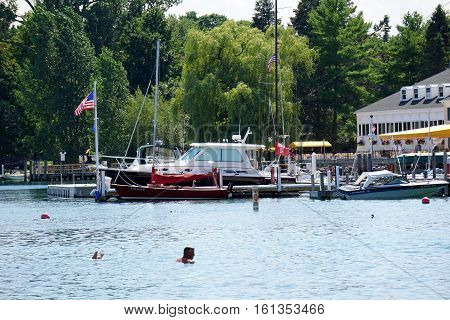 HARBOR SPRINGS, MICHIGAN / UNITED STATES - AUGUST 3, 2016: Boats are moored at private docks adjacent to the Zorn Park Public Beach near downtown Harbor Springs.