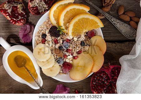 Healthy Breakfast. Muesli With Orange Fruit, Apple, Pomegranate, Nuts, Banana And Honey