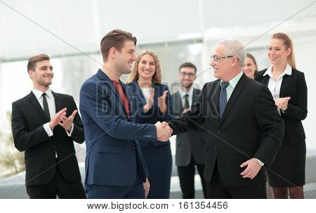 Two cheerful business people shaking hands while their colleague