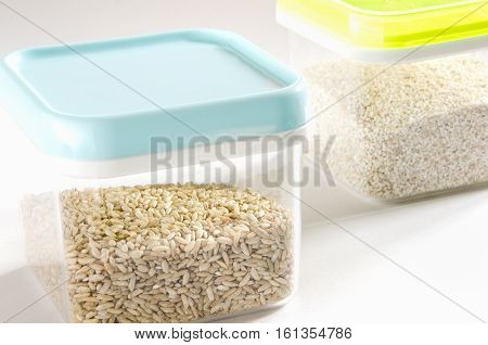 Food storage. Food ingredients (wild rice and barley) in plastic containers. Selective focus.