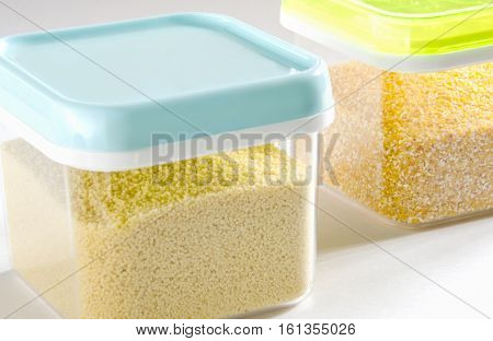 Food storage. Food ingredients (cous cous and polenta) in plastic containers. Selective focus.