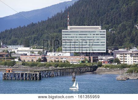 The small boat passing by the government building in Juneau the capital of Alaska.